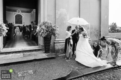 Piacenza, Italia Novia bajo un paraguas bajo la lluvia preparándose para entrar a la iglesia para la ceremonia