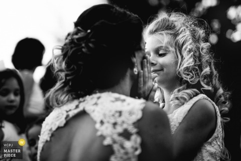 Nerac, France Wedding Photojournalist | the bride talks to a young flower girl at the outdoor reception it is black and white photo