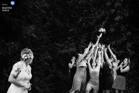 Paris Wedding Photojournalist | the bride and looks over her shoulder after throwing her bouquet to about a dozen women at this outdoor wedding reception