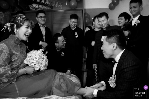 ChongQing Wedding Photojournalist | Black and white photo of the groom holding the bride with her bouquet on her lap