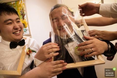 Groomsmen having fun helping the groom during traditional door games in China