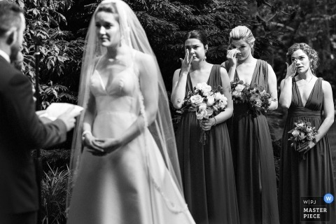 Boston Wedding Photojournalist | the groom reads his vows to the bride during their outdoor ceremony 3 bridesmaids simultaneously wipe tears