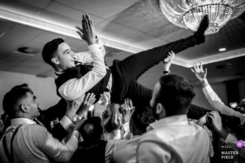 Hengelo Wedding Photojournalist | the groom is tossed above the heads of Wedding guests on the reception dance floor