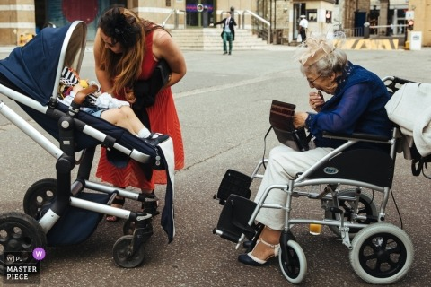 HAC, London  Wedding Photojournalist | grandma in wheelchair is facing a baby in a stroller outside of the church wedding