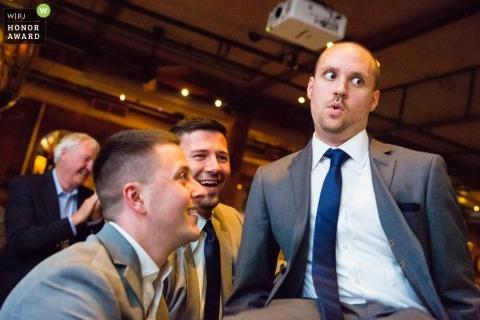 Nowożeńcy drużbowie bawią się w recepcji, podnosząc pana młodego na krześle