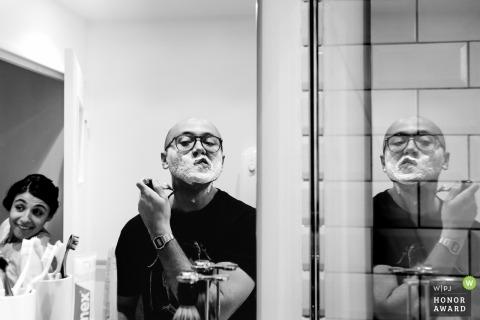 Marié rasage dans le miroir avec des reflets avant de se préparer pour le mariage à Paris