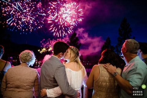 A bride and groom share a kiss under a sky full of fireworks at the end of their wedding reception in Post Falls, Idaho.
