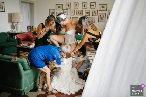 Portofino Wedding Photojournalist | the bride steps into her wedding gown with the help of friends and family