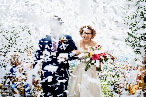 Putney, Vermont Wedding Photojournalist | the bride and groom exit during a blizzard of white confetti