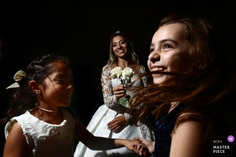 Goiânia Wedding Photojournalist | the bride enjoys time with dancing flower girls