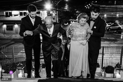 GNU - Porto Alegre - Rio Grande do Sul  Wedding Photojournalist | an elderly couple is health up the stairs to the church by Usher groomsmen