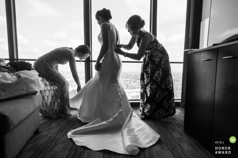 Bridesmaids help the bride get ready over a beautiful view of Detroit from the Marriott at the Renaissance Center