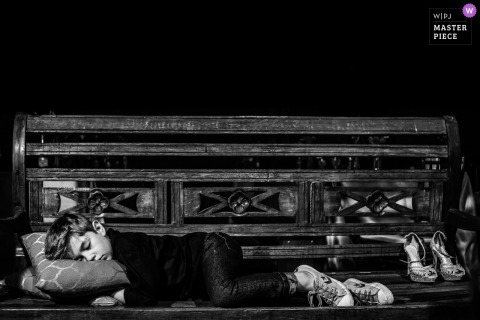 São Carlos Wedding Photojournalist | a little ringbearer sleeps with a pillow on a bench in this black-and-white photo
