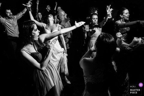 São Carlos Wedding Photojournalist | the bride is surrounded by dancing female wedding guests on the dance floor in and this black-and-white reception photo