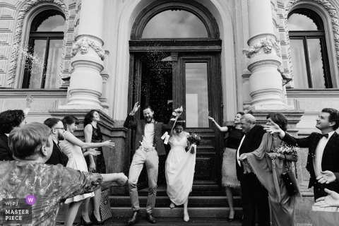 Saint-Petersburg Wedding Photojournalist | the bride and groom exit the church and are showered with flowers rice and confetti as they come down the stairs