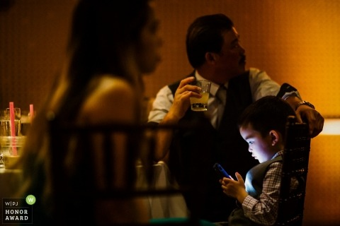 Argonaut Hotel, San Francisco - a child uses electronic game device during reception party