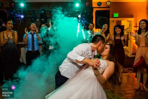 Argonaut Hotel, San Francisco wedding photograph of the groom dipping and kissing the bride on the dance floor under green fog.