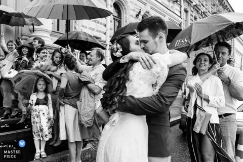 Saint-Petersburg Wedding Photojournalist | the bride and groom hug and kiss in this black-and-white photo as guests watch from the church stairs under their umbrellas in the rain