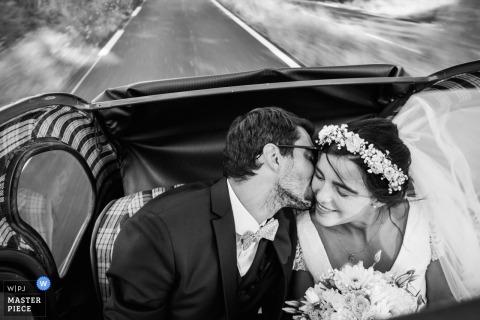 Beweging huwelijksfotografie in Beziers, FRANKRIJK | bruid en bruidegom kussen in de rug van een converteerbare auto