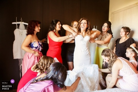 Veria Wedding Photojournalist | the bride has multiple hands and helping her fit into her dress