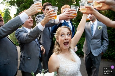 Oyster Bay, New York wedding photograph of bride toasting surrounded by groomsmen.