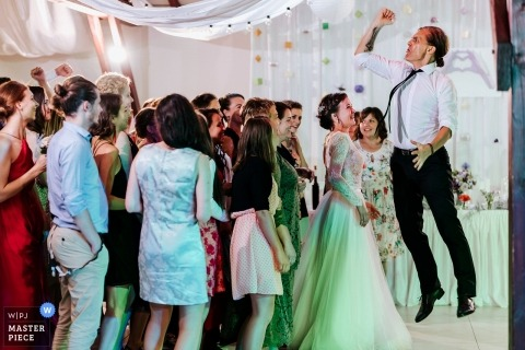 Harghita Wedding Photojournalist | a wedding guest jumps high above others on the dance floor at the reception