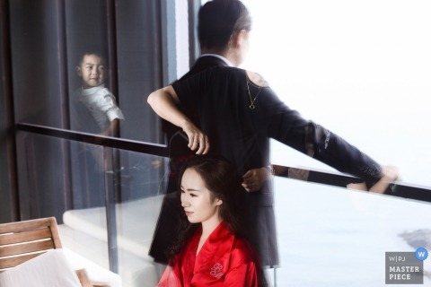 Hangzhou City Wedding Photojournalist | la novia tiene el cabello preparado para la ceremonia mientras su novio espera lo que se ve en el reflejo