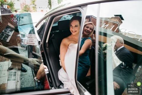 An excited bride sits the back of the car before the start of the ceremony in Alexandria