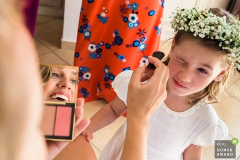 The flower girl getting make-up before the wedding in Greece - Bridal preparation in Ikaria