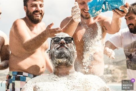 Ikaria - Greece Wedding Photojournalist | the groom receives hazing treatment from the groomsmen