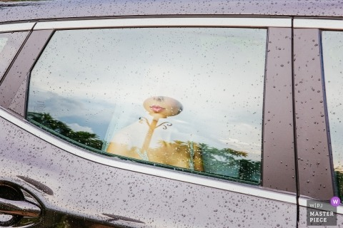 Athens - Greece Wedding Photojournalist   the bride waited in the car covered with rain droplets before the ceremony