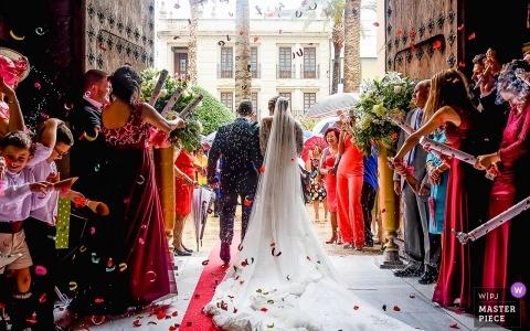 Murcia Wedding Fotojournalist | de bruid en bruidegom verlaten de kerk na de ceremonie als gasten bloembladen naar hen gooien