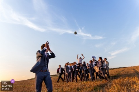 Wissant Wedding Fotojournalist | de bruidegom gooit het bruidsboeket naar een groep mannen buiten op een heuvel