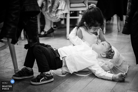 Les Rasses, Zwitserland Trouwfotojournalist | de ringdrager en bloemenmeisje Speel samen op de vloer bij de receptie