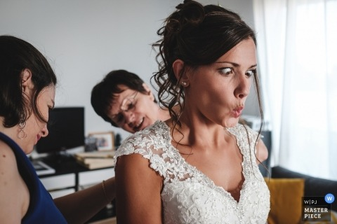 Morbihan Wedding Photojournalist | the bride crosses her eyes as she reacts to her dress being buttoned up from behind