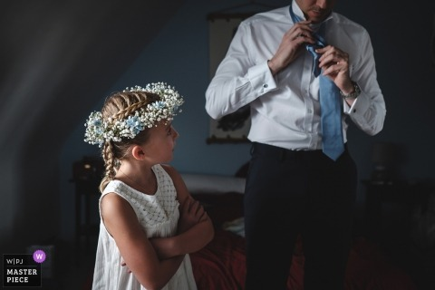 Morbihan Wedding Photojournalist | flower girl in her dress with flowers in her hair watches a man tie his tie