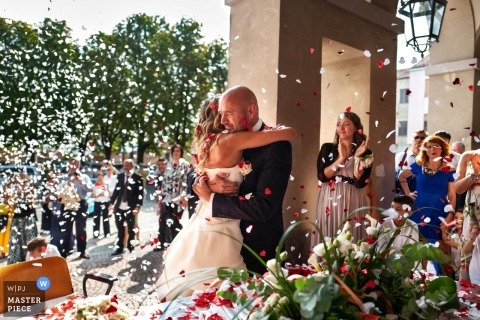 Comune di Azeglio wedding photograph of the bride and groom hugging under confetti.