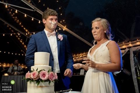 De bruid en de bruidegom glimlachen na het zetten van cake in elkaars gezichten bij een het huwelijksontvangst van Key West Florida