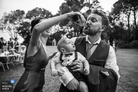 Hérault Wedding Photojournalist | South of France a wedding guest is help with his drink as he holds a small boy in suspenders and a bowtie