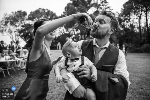 Fotojournalist Hérault Wedding | Zuid-Frankrijk een bruiloftsgast is hulp bij zijn drankje terwijl hij een jongetje in jarretels en een strikje vasthoudt