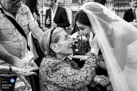 Fotojournalist van Sicilia Wedding | grootmoeder raakt zachtjes de bruiden gezicht onder haar sluier na de ceremonie