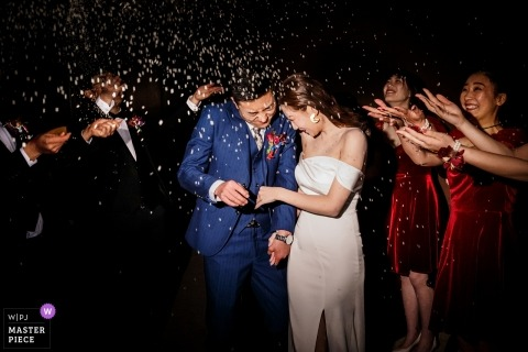 Shandong Wedding Photojournalist | the bride and groom are showered with confetti by guests as they exit the wedding reception at night
