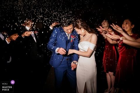 Shandong Wedding Photojournalist | de bruid en bruidegom worden door gasten overladen met confetti als ze 's nachts de huwelijksreceptie verlaten
