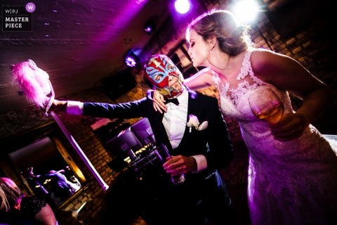 North Rhine-Westphalia Wedding Photojournalist | Mexican wrestling mask on the groom as he dances with the bride at the reception