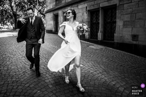 North Rhine-Westphalia Wedding Photojournalist | the bride and groom walked quickly down a cobblestone street on wedding day