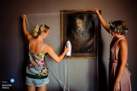 Fotojournalist van Hesse Wedding | de bruid stookt haar sluier terwijl ze zich klaar maakt in Duitsland