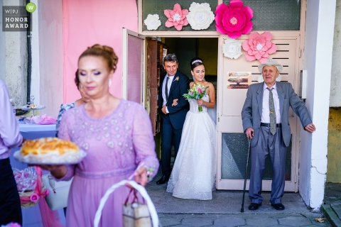 Kozloduj, Bulgaria bride and groom exit a building with family members carrying food