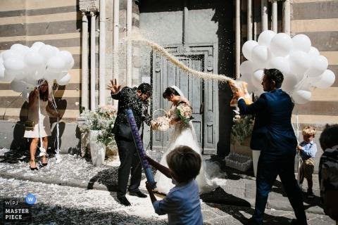 Portofino Hochzeitsfotojournalist | Kinder halten Luftballons in der Hand, während Reis auf die Braut und den Bräutigam wirft, die die Kirche verlassen