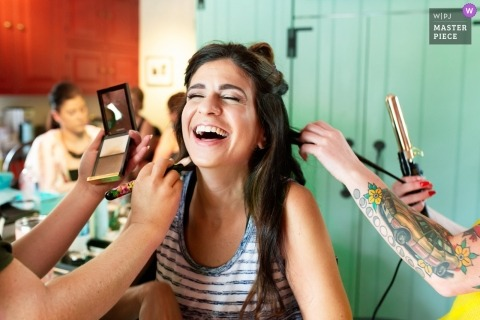 Pennsylvania Wedding Photojournalist | the bride is helped curling her hair and applying makeup while getting ready