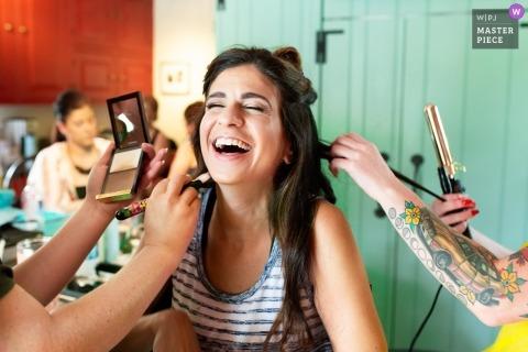 Pensilvania fotoperiodista de bodas | La novia es ayudada a rizar su cabello y aplicar maquillaje mientras se prepara.